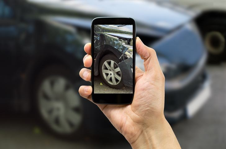 Man using smartphone to take picture of accident