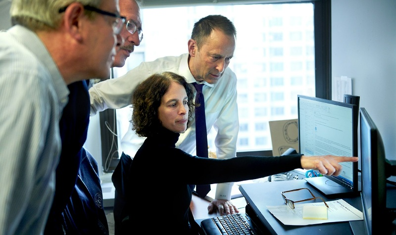 three lawyers gather around an analyst pointing at a computer screen